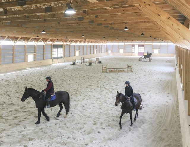 horses riding around new construction riding arena