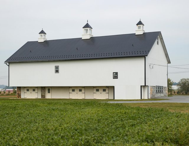 white vinyl barn with black metal roof